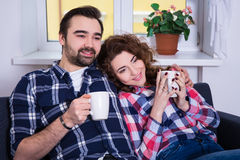Happy young couple sitting on sofa with cups of tea or coffee Stock Photography