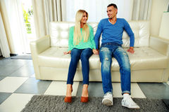 Happy young couple sitting on the sofa Royalty Free Stock Images
