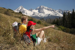 Happy young couple sitting on spring mountains mea Royalty Free Stock Images