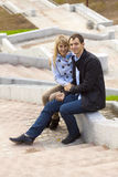 Happy young couple sitting on stairs. Smiling Stock Photo
