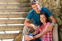 Happy young couple sitting on stairs smiling Stock Photos