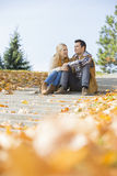 Happy young couple sitting on steps in park Stock Photography