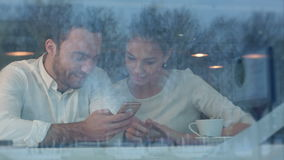 Happy young couple sitting at table using phone in cafeteria. Viewed through the window. Professional shot on BMCC RAW with high dynamic range. You can use it e stock video