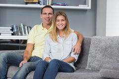 Happy young couple sitting on their couch Royalty Free Stock Photo