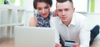 Happy young couple sitting together on the floor with laptop Stock Photo