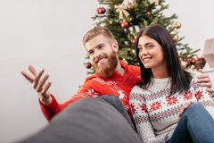 Happy couple at christmastime. Happy young couple sitting together on sofa and looking away at christmastime stock image