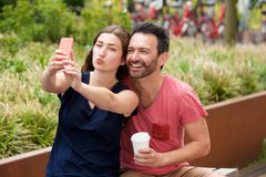 Happy young couple sitting together taking selfie on smart phone Stock Photography