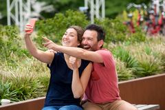Happy young couple sitting together taking selfie on smart phone Stock Image