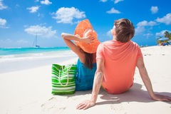 Happy young couple sitting on a tropical beach in Stock Photography