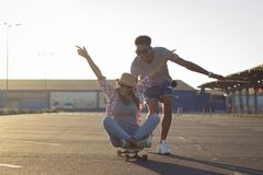 Male and female skateboarders having fun in morning mall parking. Happy young couple with skateboard, concept of happiness, love and youth Royalty Free Stock Photos