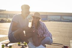 Male and female skateboarders having fun in morning mall parking. Happy young couple with skateboard, concept of happiness, love and youth Royalty Free Stock Image