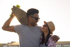 Male and female skateboarders having fun in morning mall parking. Happy young couple with skateboard, concept of happiness, love and youth Stock Photos
