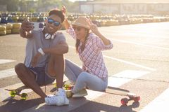 Male and female skateboarders having fun in morning mall parking. Happy young couple with skateboard, concept of happiness, love and youth Royalty Free Stock Photo