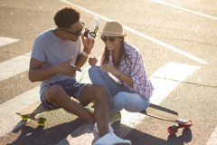Male and female skateboarders having fun in morning mall parking. Happy young couple with skateboard, concept of happiness, love and youth Stock Photography