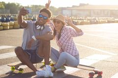 Male and female skateboarders having fun in morning mall parking. Happy young couple with skateboard, concept of happiness, love and youth Royalty Free Stock Photography