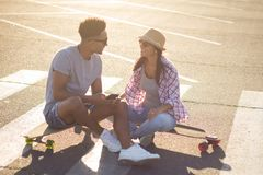 Male and female skateboarders having fun in morning mall parking. Happy young couple with skateboard, concept of happiness, love and youth Royalty Free Stock Images