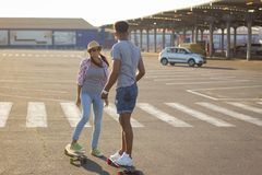 Male and female skateboarders having fun in morning mall parking. Happy young couple with skateboard, concept of happiness, love and youth Stock Image