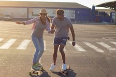 Male and female skateboarders having fun in morning mall parking stock images