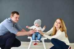 Happy young couple with small baby siting on dark background Stock Image