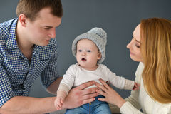 Happy young couple with small baby siting on dark background. Young couple with small baby siting on dark background Stock Image
