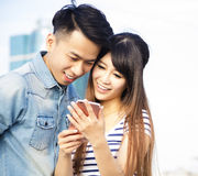 Happy young couple with smart phone Royalty Free Stock Image