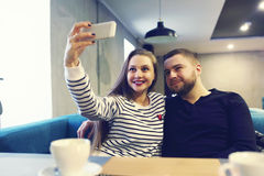 Happy young couple with smartphone taking selfie at cafe in mall. sale, shopping, consumerism, technology and people. Sale, shopping, consumerism, technology and Stock Images