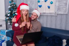 Happy couple, on the eve of the new year, doing online shopping, a girl looking at a credit card. Happy young couple smiling, doing online shopping, on New Year Stock Photo