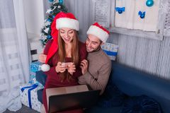 Happy couple, on the eve of the new year, doing online shopping, a girl looking at a credit card. Happy young couple smiling, doing online shopping, on New Year Royalty Free Stock Photos
