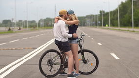 Happy young couple smiling laughing riding bicycle, slow motion. stock video