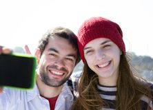 Happy young couple smiling and taking selfie with mobile phone Royalty Free Stock Images