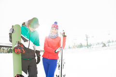 Happy young couple with snowboard and skis in snow Royalty Free Stock Image