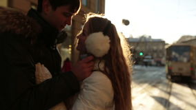 Happy young couple softly kissing on sunset in winter. City life and traffic jam on background stock video footage
