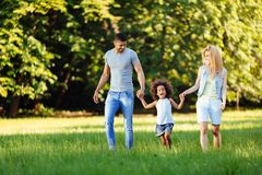 Happy young couple spending time with their daughter. In nature Stock Photo