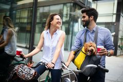 Happy young couple spending time together with dog and bicycles. Attractive women and handsome men spending time together with dog and bicycles stock image