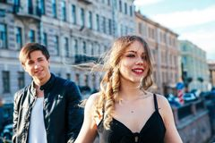 Happy couple is spending vacation holidays in St. Petersburg. Both look really happy. They are strolling along the streets of the Stock Image