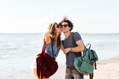 Happy young couple standing at the beach and kissing Royalty Free Stock Photo