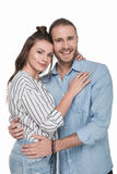 Happy young couple standing embracing and smiling at camera. Isolated on white Royalty Free Stock Images