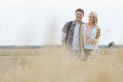 Happy young couple standing at field Royalty Free Stock Photography