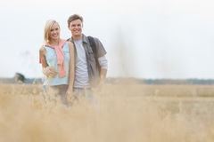 Happy young couple standing at field Royalty Free Stock Photos