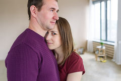Happy young couple standing in the light room. Portrait of man and woman looking at camera at home. Happy young couple standing in the light room. Portrait of Royalty Free Stock Image