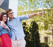 Happy young couple standing at street of city and laughing on the bright sunny day. Happy funny couple standing outdoors at street of city and laughing on the Royalty Free Stock Images