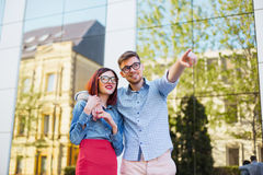 Happy young couple standing at street of city and laughing on the bright sunny day. Happy funny couple standing outdoors at street of city and laughing on the Stock Image