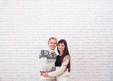 Happy young couple standing together over white brick background Stock Photos