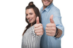 Happy young couple standing together and showing thumbs up sign. Close-up view of happy young couple standing together and showing thumbs up sign Stock Image