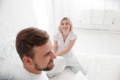 Beautiful young couple together in bed. Happy couple in bedroom on a white background. Stock Images