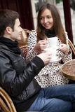 Happy young couple in a street cafe royalty free stock photos