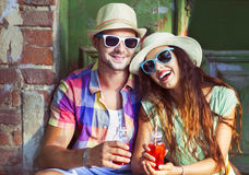 Happy young couple in the street wearing hats and sunglasses royalty free stock photo