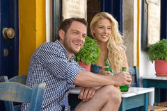 Happy young couple in summer holidays at outdoor restaurant. Royalty Free Stock Photos