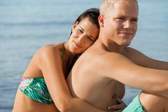 Happy young couple sunbathing. Happy attractive affectionate young couple sunbathing together on the beach in their swimwear while enjoying a tropical summer Royalty Free Stock Photo