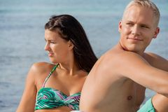 Happy young couple sunbathing. Happy attractive affectionate young couple sunbathing together on the beach in their swimwear while enjoying a tropical summer Royalty Free Stock Images